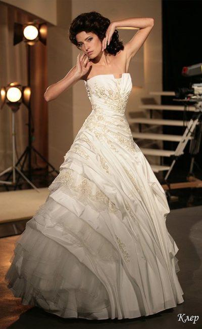Великолепное свадебное платье пышного кроя с фактурными драпировками и кружевным декором.