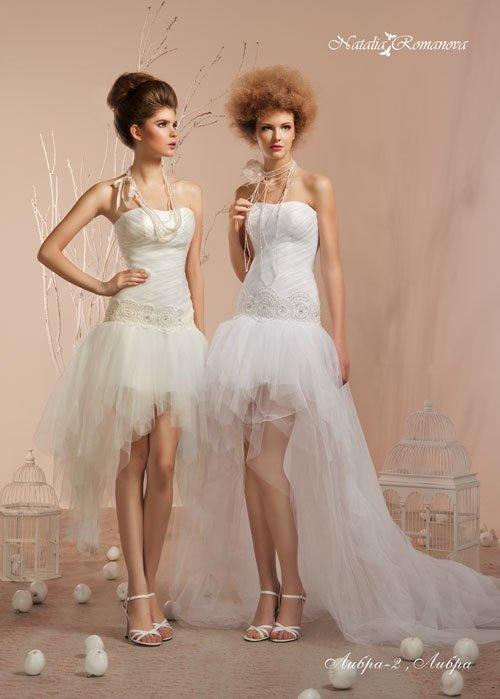 Свадебное платье с открытым лифом и короткой юбкой, дополненной пышным длинным шлейфом.