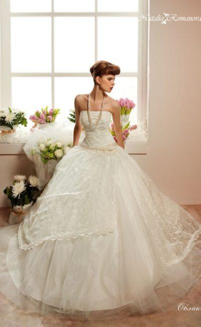 Свадебное платье с лифом прямого кроя и многослойной юбкой с кружевным декором.