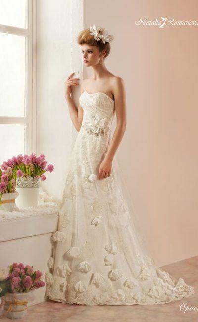 Открытое свадебное платье цвета «слоновой кости» с объемной отделкой по всей длине.