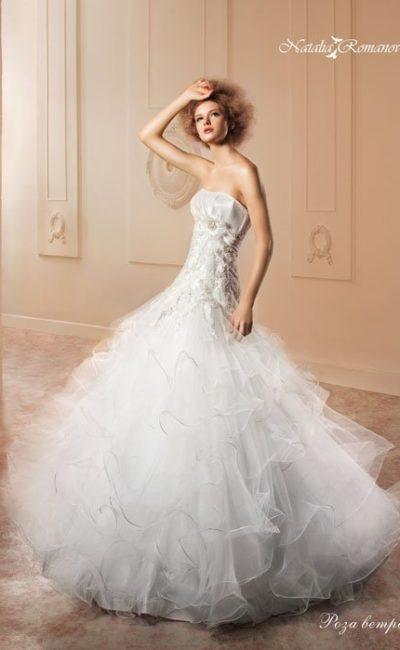 Торжественное свадебное платье с пышной полупрозрачной юбкой и открытым корсетом с объемным декором.