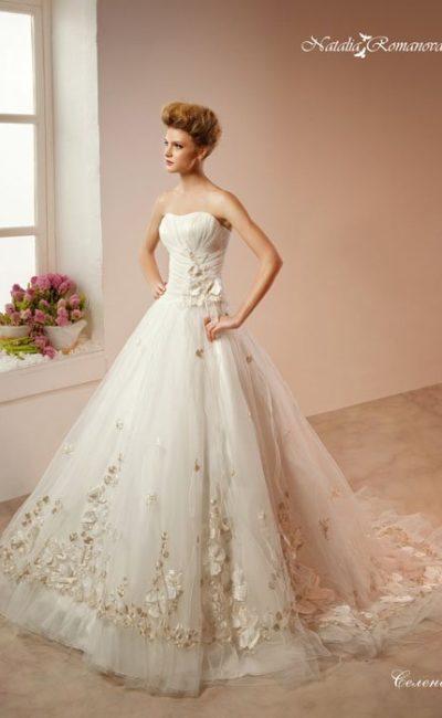 Свадебное платье с роскошной многослойной юбкой, покрытой объемными лепестками.