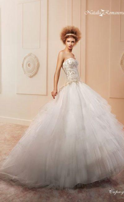 Открытое свадебное платье с золотистой кружевной отделкой корсета и потрясающей юбкой.