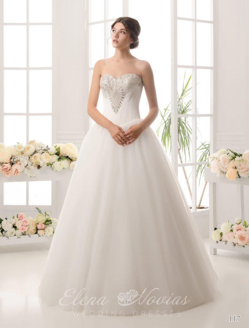 Свадебное платье с открытым лифом, украшенным бисерной вышивкой, и пышной юбкой.