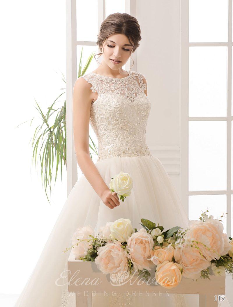 Закрытое свадебное платье с многослойной юбкой и украшенным вышивкой поясом на талии.