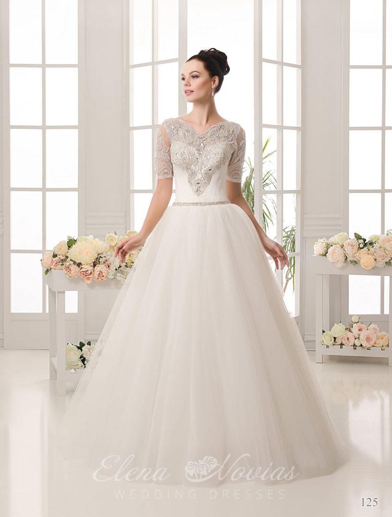 Пышное свадебное платье, декорированное серебристым бисером и дополненное короткими рукавами.