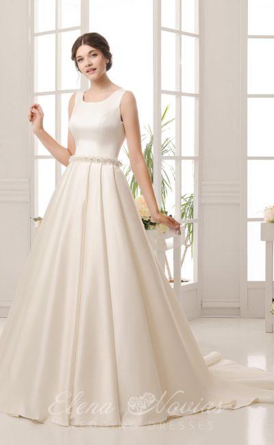 Лаконичное свадебное платье с округлым вырезом декольте и объемным бисерным поясом.