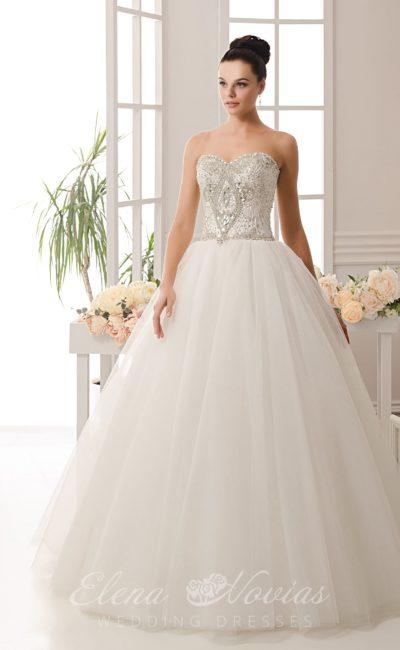 Торжественное свадебное платье с многослойной пышной юбкой и сверкающим открытым корсетом.