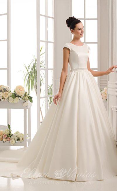 Лаконичное свадебное платье с округлым вырезом, короткими рукавами и блестящим поясом.