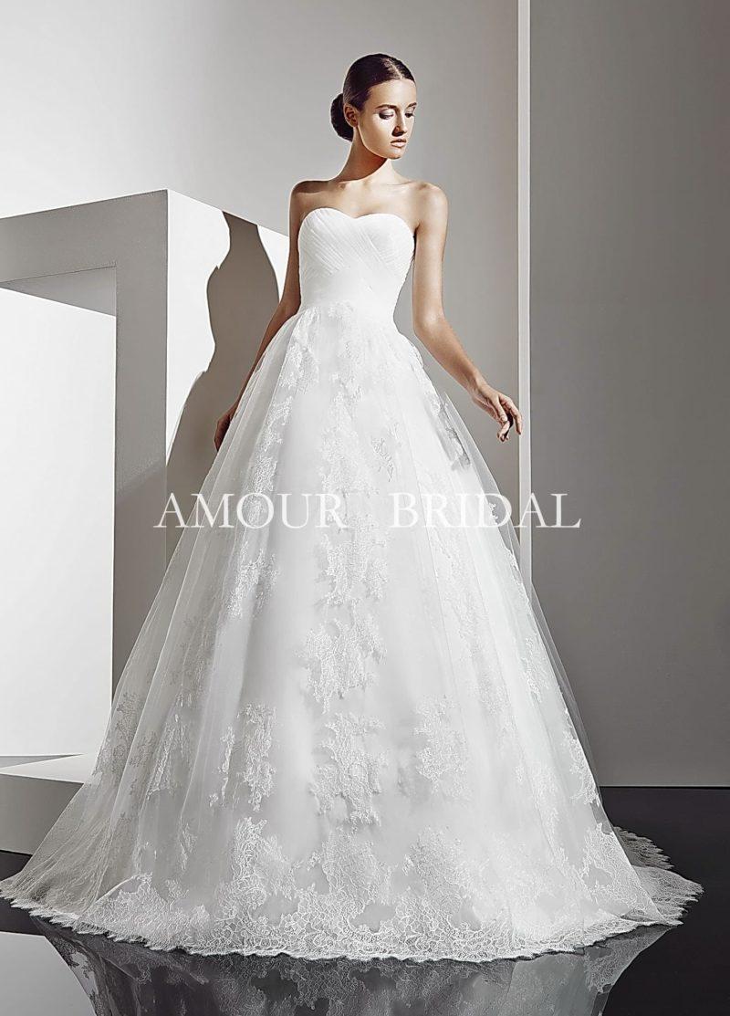 Стильное свадебное платье пышного кроя с лаконичным корсетом и украшенной кружевом юбкой.