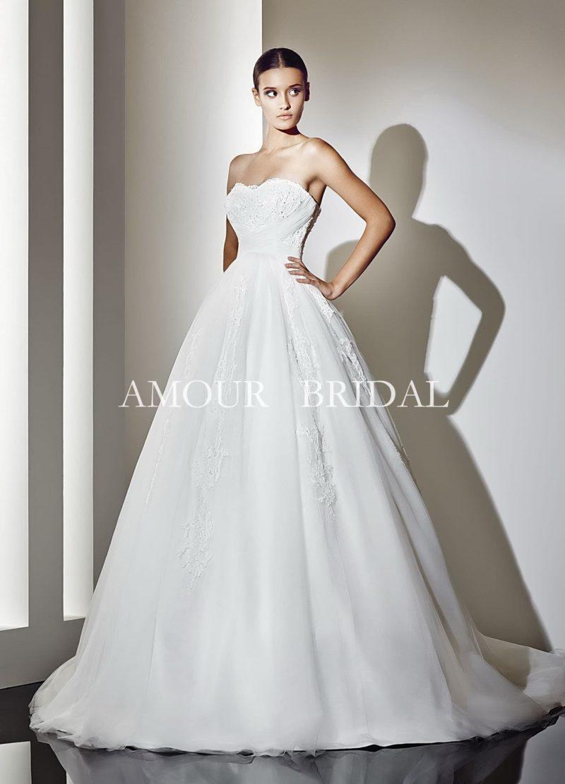 Элегантное свадебное платье с изящным открытым декольте и многослойной юбкой со шлейфом.