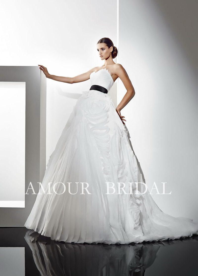 Драматичное свадебное платье с оборками по пышной юбке и броским черным поясом из атласа.