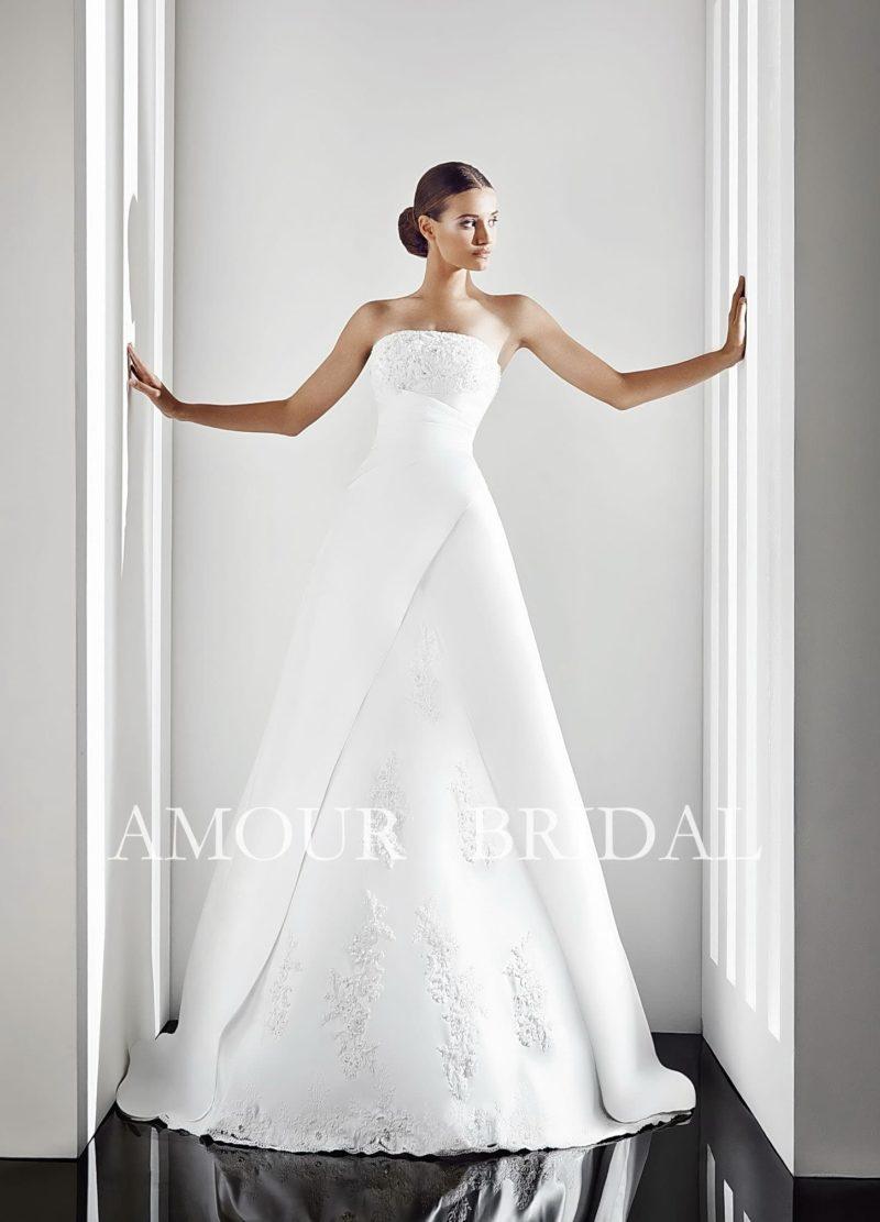 Впечатляющее свадебное платье с драматичной драпировкой атласа на корсете и открытым лифом.