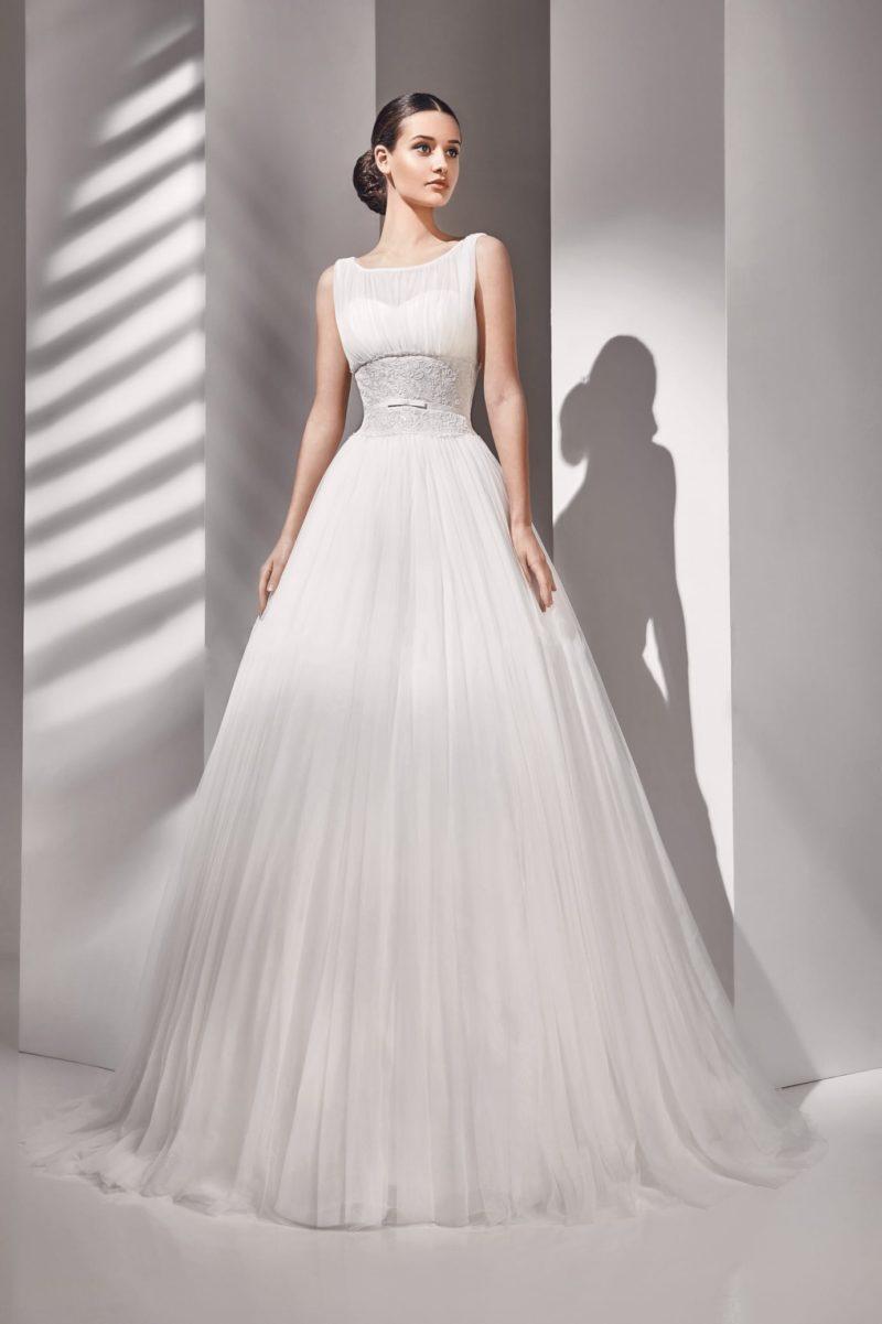 Пышное свадебное платье с полупрозрачным декором лифа и кружевом на талии.