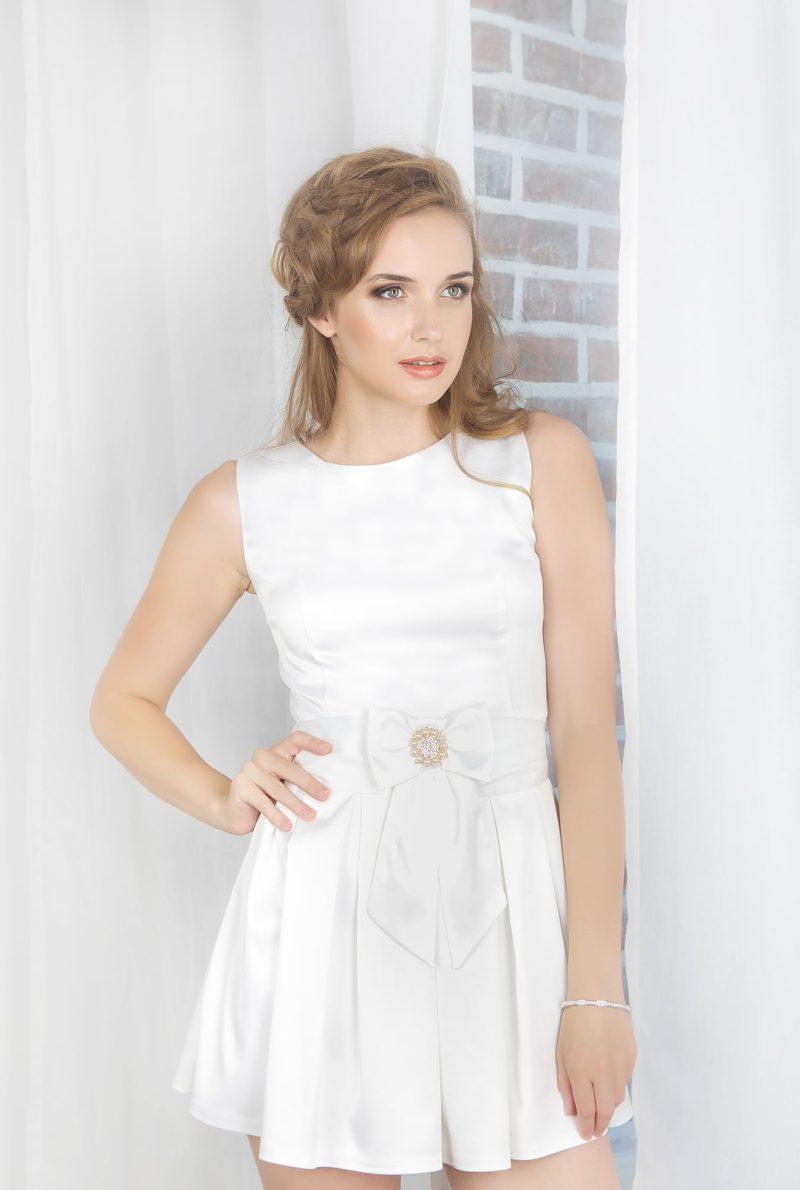 Короткое вечернее платье белого цвета с бантом на талии и округлым вырезом под горло.