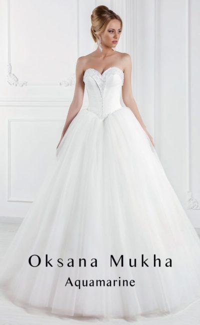 Торжественное свадебное платье пышного кроя с атласным корсетом и вышивкой по краю декольте.