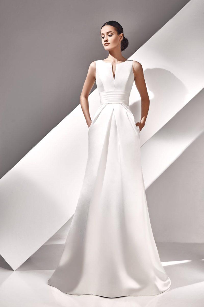 Свадебное платье из атласа с графичным лифом и широким поясом на талии.