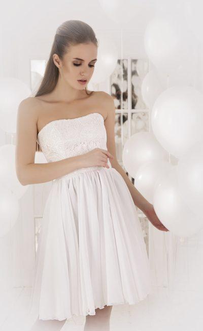 Нежное вечернее платье белого цвета с открытым лифом прямого кроя и короткой юбкой.