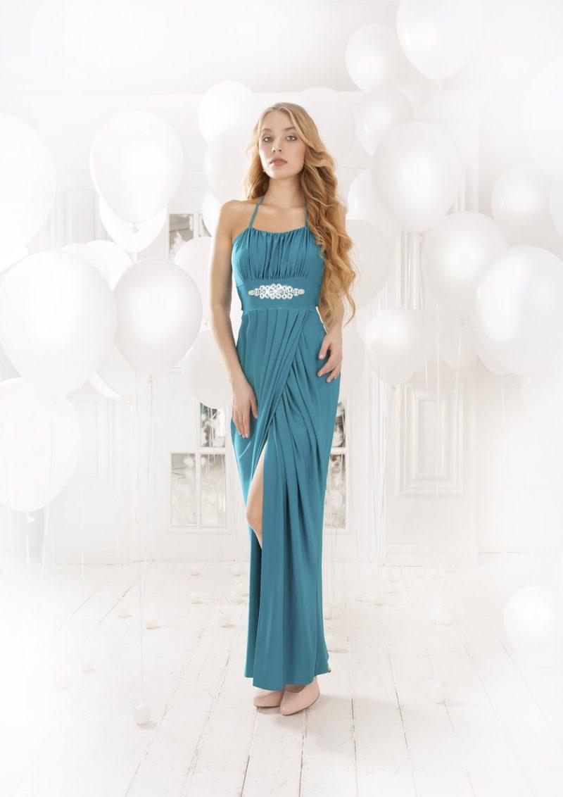 Оригинальное вечернее платье прямого кроя с драпировками и разрезом на юбке, а также открытой спиной.