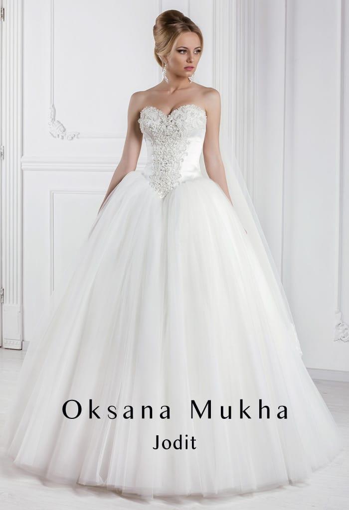 Свадебное платье с объемной юбкой с полупрозрачным верхом и элегантным открытым корсетом.