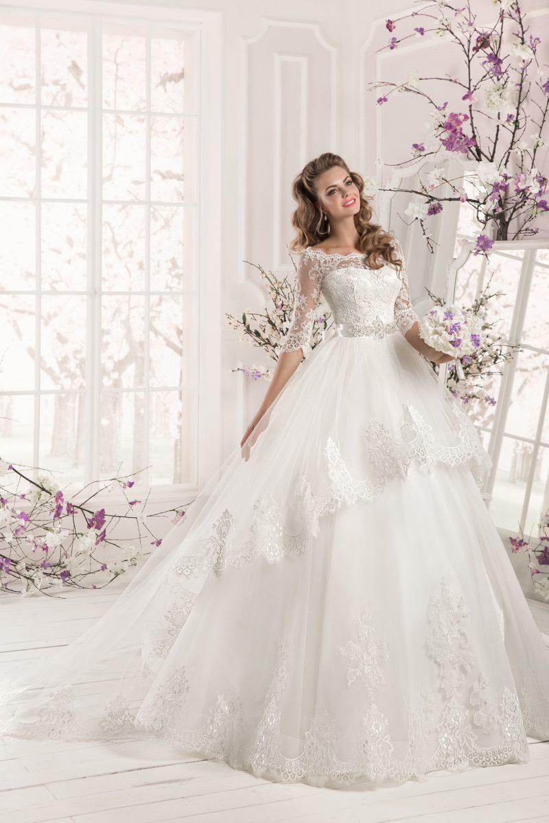 Роскошное свадебное платье с длинной кружевной баской, округлым декольте и сияющим поясом.