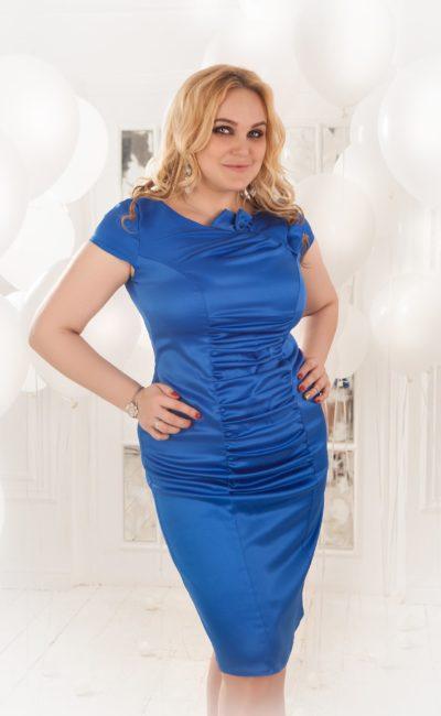 Атласное вечернее платье-футляр с коротким рукавом и юбкой длиной до линии коленей.