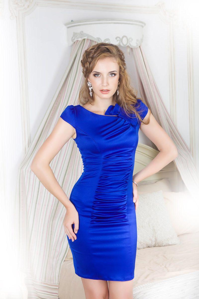 Облегающее вечернее платье из синего атласа, украшенного драпировками.
