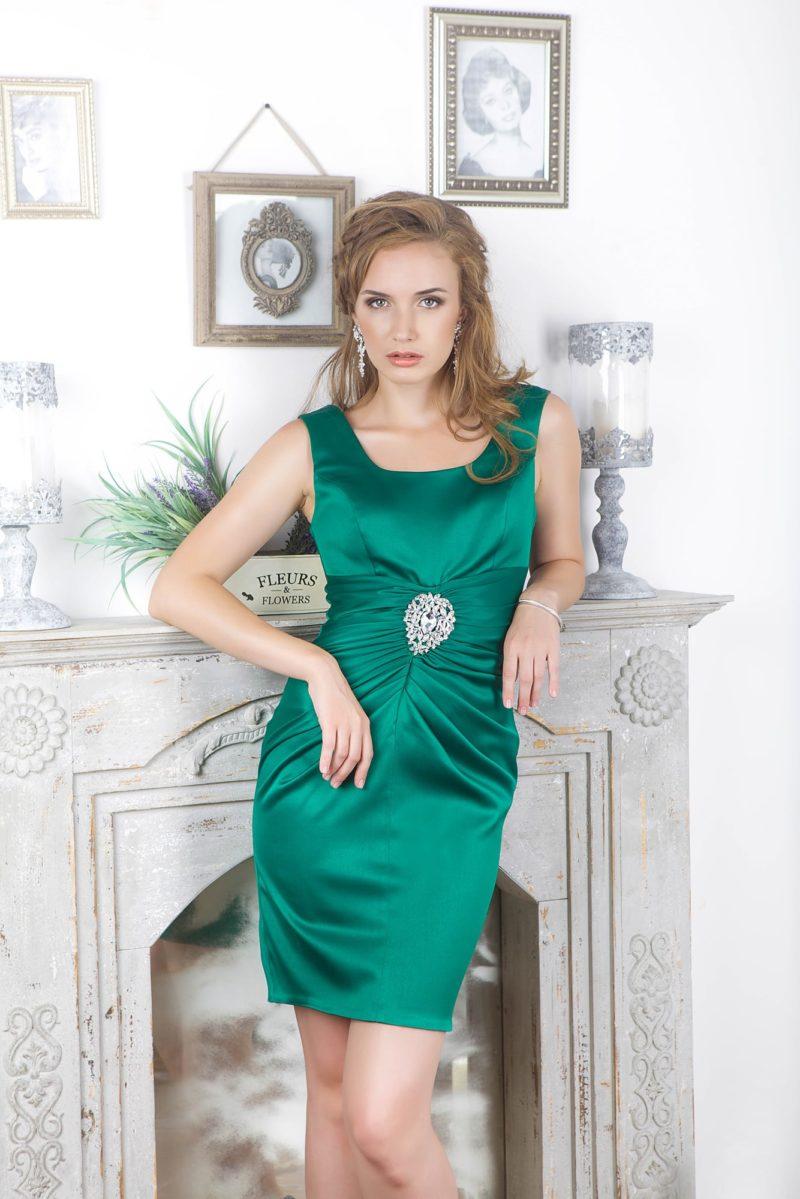 Изумрудно-зеленое вечернее платье-футляр с округлым декольте и длиной до колена.