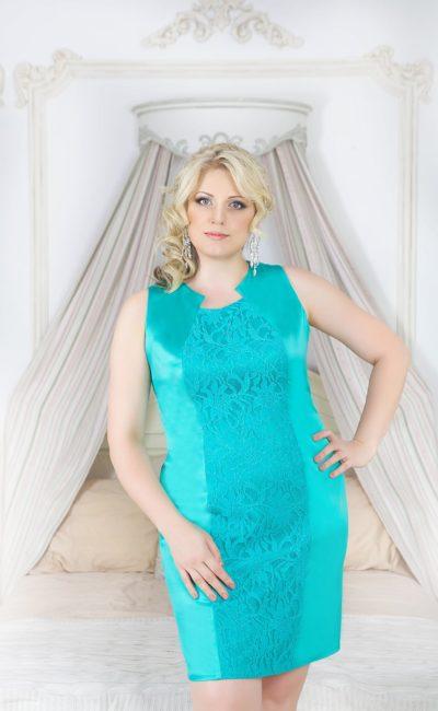 Атласное вечернее платье с фигурным вырезом, пышной баской и юбкой до колена.