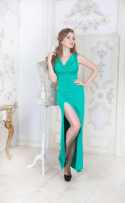 Прямое вечернее платье изумрудного цвета с воротником-хомутом и разрезом на юбке.