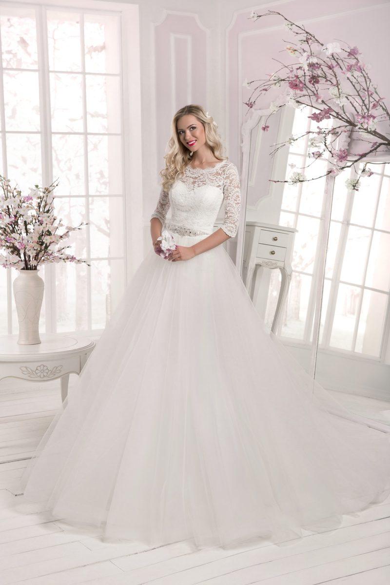 Пышное свадебное платье с закрытым кружевным верхом и поясом, украшенным бисером.