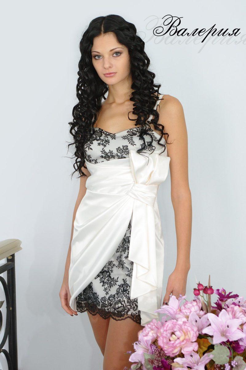 Белое вечернее платье из атласной ткани с отделкой черным кружевом.