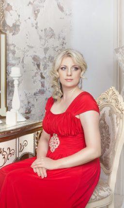 Прямое вечернее платье красного цвета с широким поясом, украшенным бисером, и коротким рукавом.