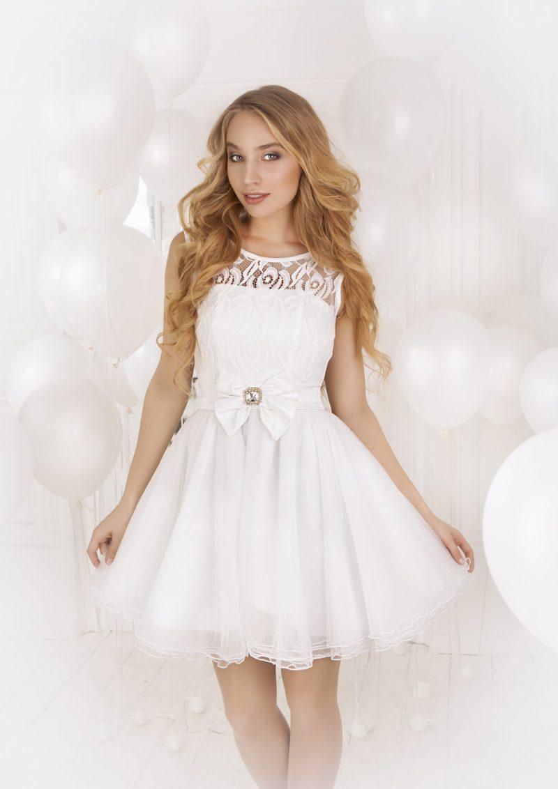 Пышное вечернее платье длиной до колена, выполненное из ткани белого цвета, с кружевным верхом.