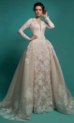 Кремовое свадебное платье с кружевной отделкой и пышной верхней юбкой со шлейфом.