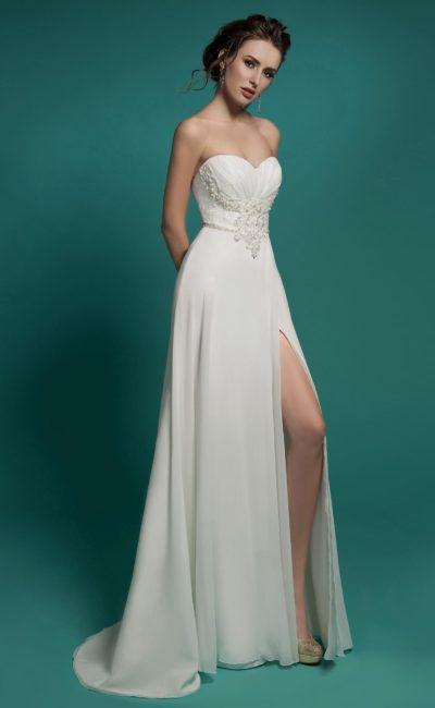 Прямое свадебное платье с открытым лифом-сердечком и отделкой из драпировок и аппликаций.