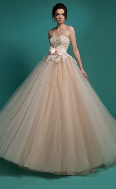 Шикарное свадебное платье золотистого цвета с открытым корсетом, покрытым кружевным декором.