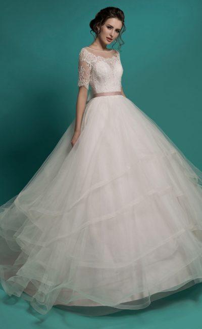 Пышное свадебное платье с округлым вырезом и многоярусной юбкой с объемным шлейфом.