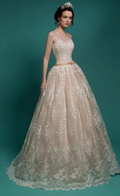 Бежевое свадебное платье с кружевным декором и атласным поясом в тон ткани подкладки.