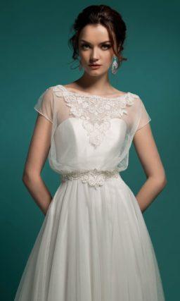 Очаровательное свадебное платье пышного кроя с полупрозрачной отделкой верха с округлым вырезом.
