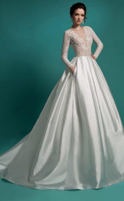 Стильное свадебное платье с кружевным верхом и объемной атласной юбкой со скрытыми карманами.