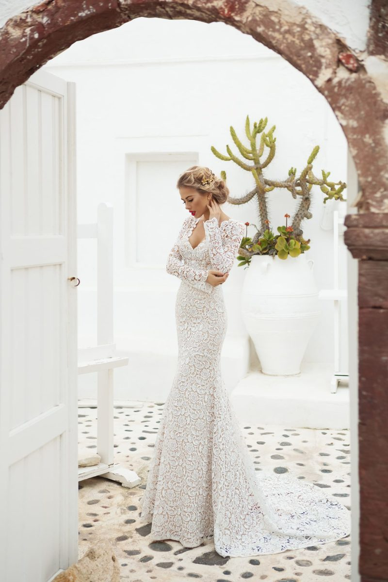 Потрясающее свадебное платье из кружевной ткани, открывающее декольте и дополненное длинным рукавом.