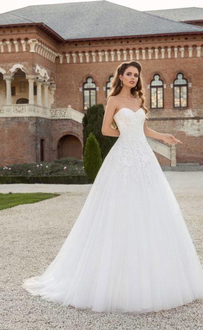 Лаконичное свадебное платье пышного силуэта с открытым корсетом традиционного кроя.
