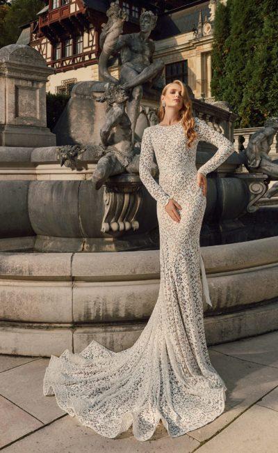 Великолепное свадебное платье из плотной кружевной ткани, с округлым вырезом и длинным рукавом.