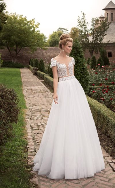 Свадебное платье с полупрозрачным верхом, покрытым кружевными аппликациями.