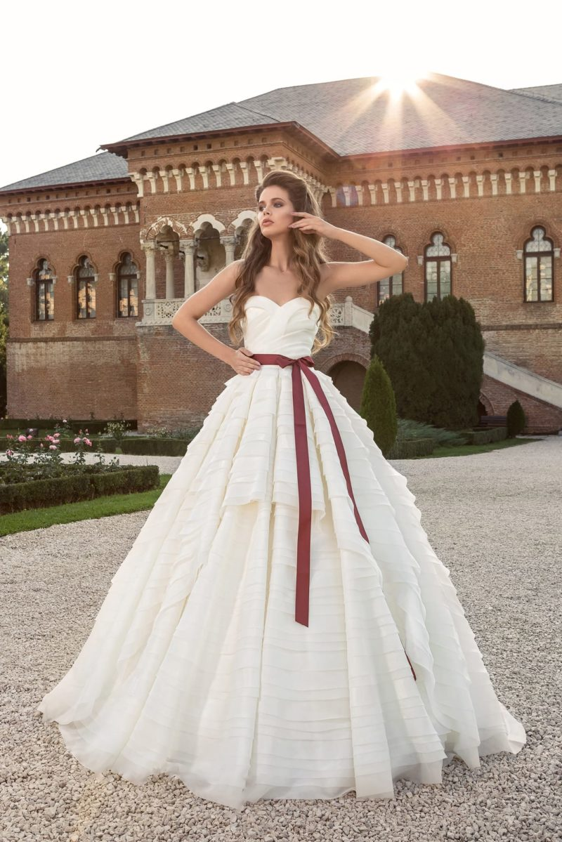 Открытое свадебное платье с изящным лифом, цветным поясом и пышной многослойной юбкой.