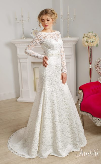 Закрытое свадебное платье с плотной кружевной отделкой, длинным рукавом и небольшим шлейфом.