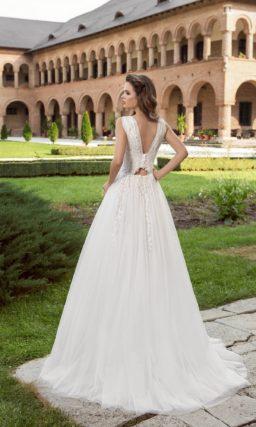 Утонченное свадебное платье с V-образными вырезами на лифе и спинке, украшенное кружевом.