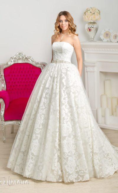 Роскошное свадебное платье с открытым лифом прямого кроя и кружевным декором юбки.