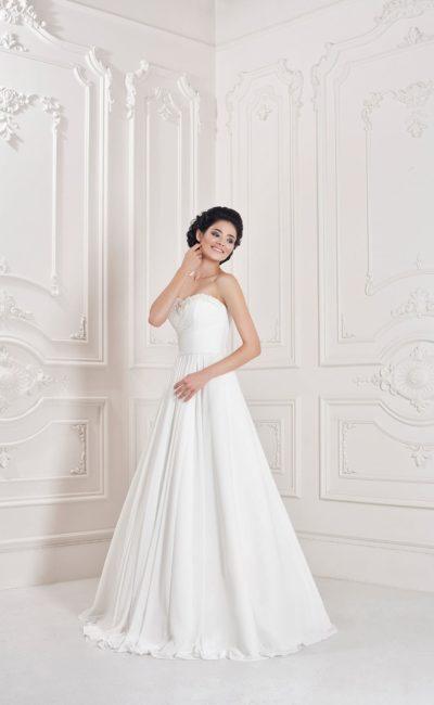 Свадебное платье с лифом в форме сердечка и лаконичной юбкой с вертикальными складками ткани.